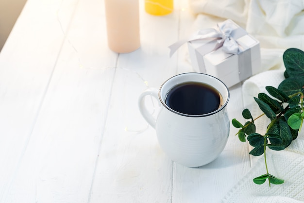 Xícara de café com o lenço feito malha em ficar na bandeja de madeira na cama, copie o espaço. bom dia pequeno almoço Foto Premium