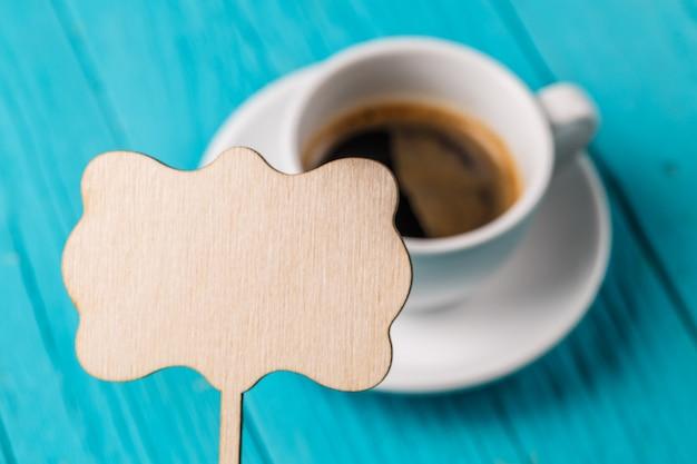 Xícara de café com placa vazia para desejos na mesa de madeira azul Foto Premium