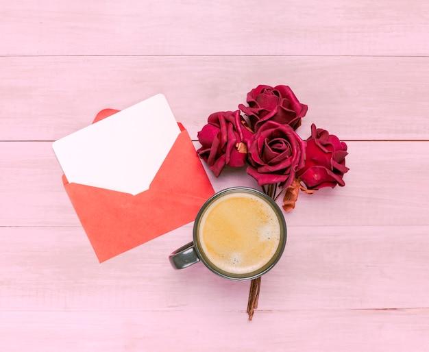 Xícara de café com rosas vermelhas e envelope Foto gratuita