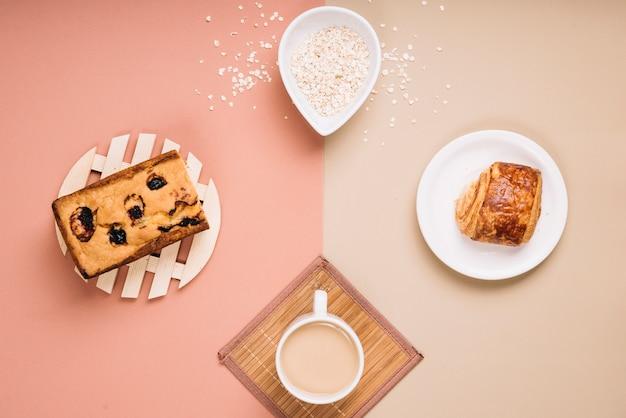 Xícara de café com torta e pão na mesa Foto gratuita