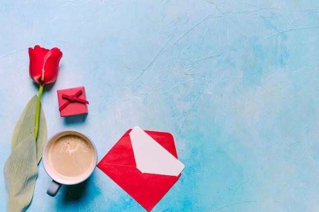 Xícara de café com tulipa vermelha na mesa Foto gratuita