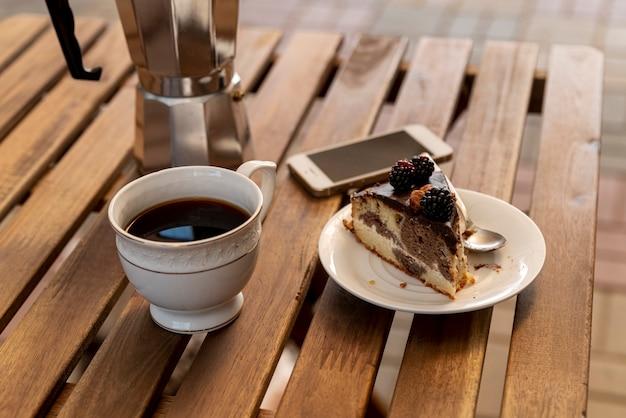 Xícara de café com uma fatia de bolo na mesa Foto gratuita
