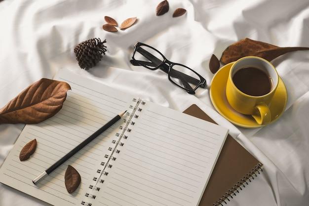 Xícara de café da letra do bloco de notas e um livro com uma cobertura em uma matéria têxtil branca na cama. Foto Premium