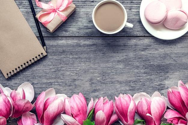 Xícara de café da manhã com leite, macaron de bolo, presente ou caixa de presente e flores de magnólia na mesa de madeira rústica. configuração plana Foto Premium