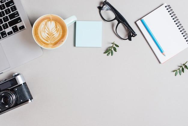 Xícara de café de cappuccino; computador portátil; câmera retro; bloco de notas adesivo; óculos e lápis no bloco de notas em espiral contra o pano de fundo branco Foto gratuita