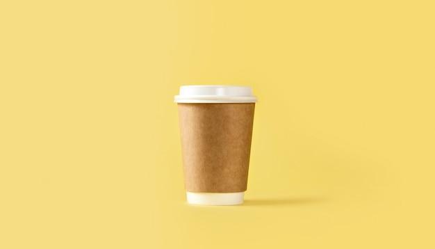 Xícara de café de papel com tampa branca em fundo amarelo Foto Premium