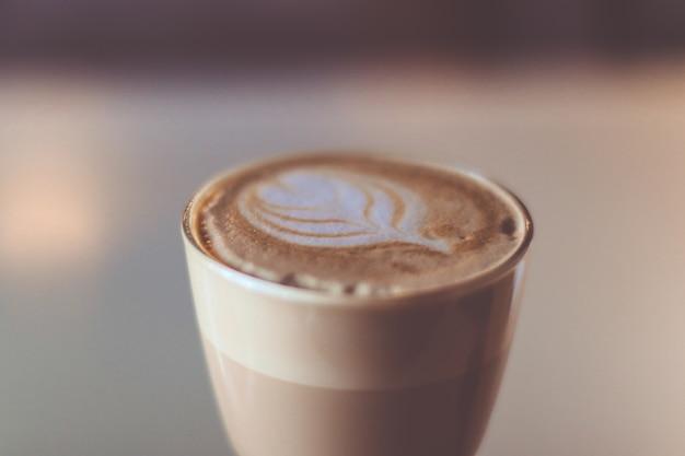 Xícara de café de vidro na tabela no café. latte quente com fundo desfocado Foto Premium