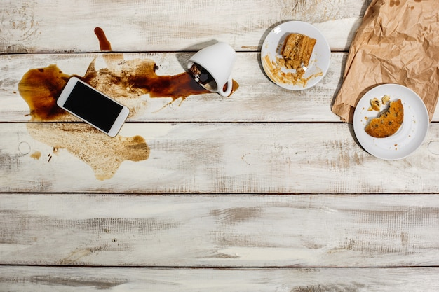 Xícara de café derramado na mesa de madeira Foto gratuita