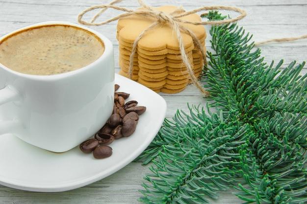 Xícara de café e biscoitos de natal, no fundo dos ramos de abeto. o feriado chega até nós. Foto Premium