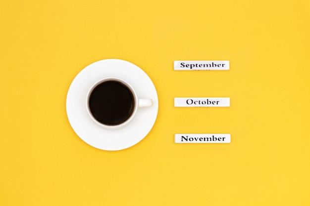 Xícara de café e calendário de novembro outubro de setembro no fundo amarelo Foto Premium