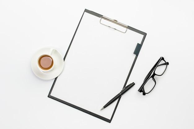 Xícara de café e caneta com papel branco na área de transferência contra a mesa de escritório Foto gratuita