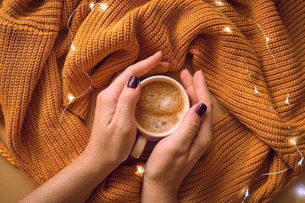 Xícara de café e com mãos de mulher, camisola amarela. Foto Premium