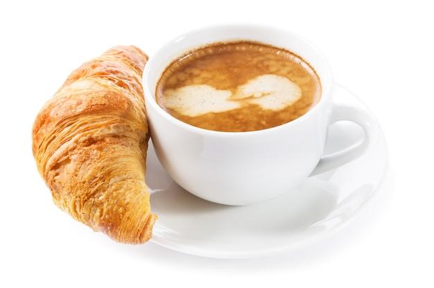 Xícara de café e croissant isolados no fundo branco Foto Premium