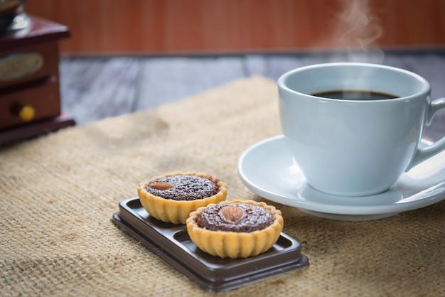 Xícara de café e grãos de café com tortas de brownie Foto Premium