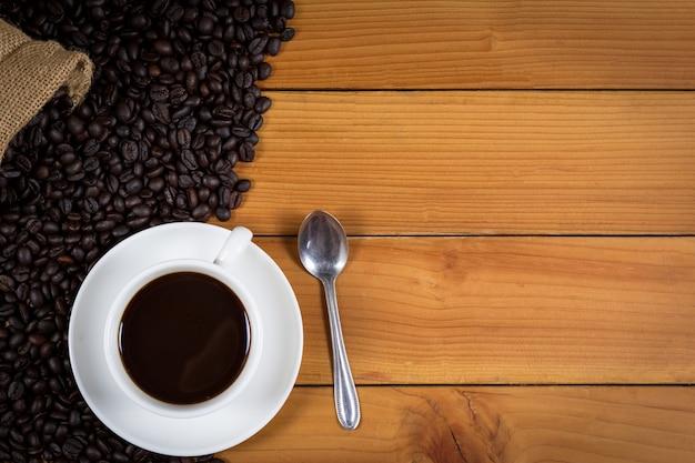 Xícara de café e grãos de café em um saco na madeira Foto Premium
