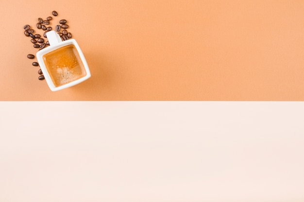 Xícara de café e grãos de café torrados em duplo cenário Foto gratuita