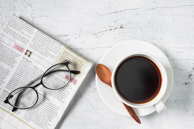 Xícara de café e jornal da manhã na mesa de madeira branca Foto Premium