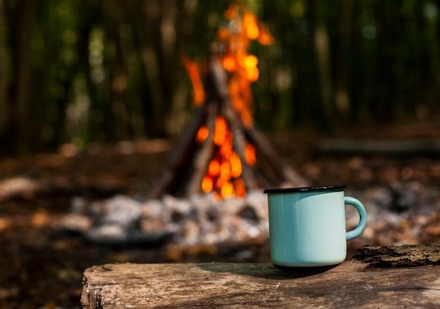 Xícara de café e madeira queimada turva no fundo Foto Premium