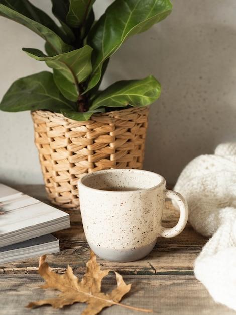 Xícara de café e planta na panela na mesa de madeira Foto Premium