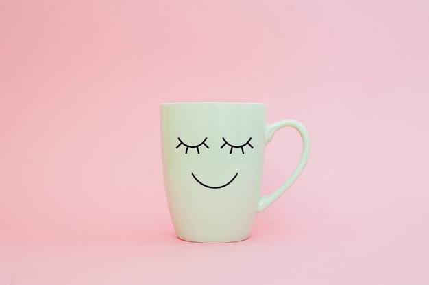 Xícara de café em fundo rosa com cara de sorriso feliz Foto Premium
