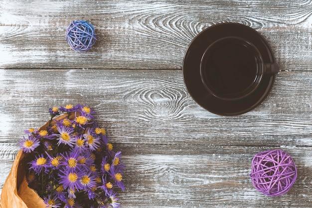 Xícara de café, flor embrulhada em papel kraft na mesa cinza de cima. estilo pastel liso leigo. Foto Premium
