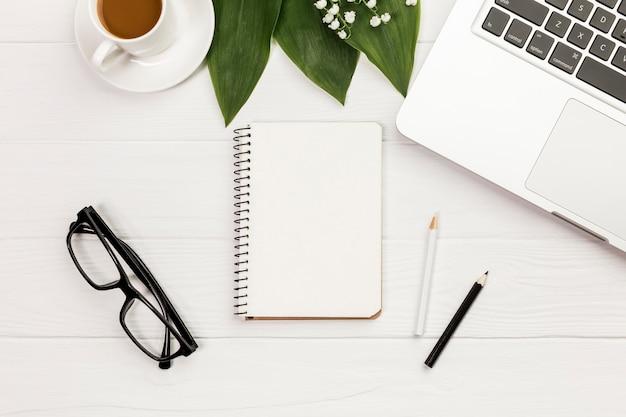 Xícara de café, folhas, bloco de notas em espiral, óculos na mesa de madeira de escritório Foto gratuita