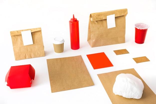 Xícara de café; garrafa de molho; beber; hambúrguer e pacote em fundo branco Foto gratuita