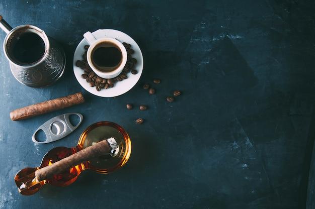 Xícara de café, grãos de café, cinzeiro com charuto no escuro Foto Premium