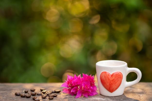 Xícara de café, grãos de café torrados e buganvílias flor na placa de madeira. Foto Premium