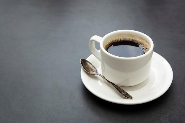 Xícara de café isolada. xícara de café branca vista superior colher e prato em fundo escuro Foto Premium