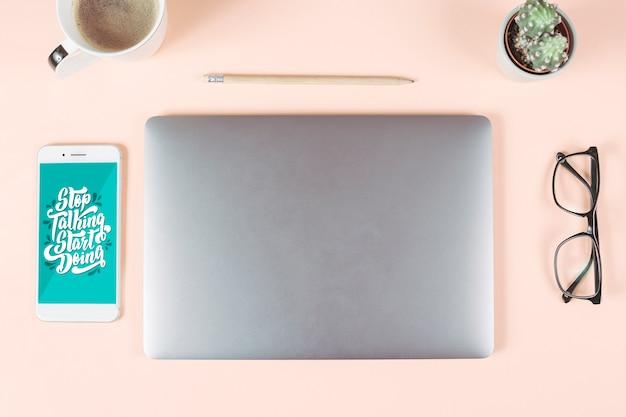 Xícara de café; lápis; óculos; pote de cacto; telefone inteligente e laptop em fundo colorido Foto gratuita
