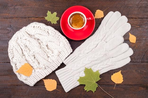 Xícara de café, luvas, chapéu de malha artesanal e folhas de outono em tábuas de madeira Foto Premium