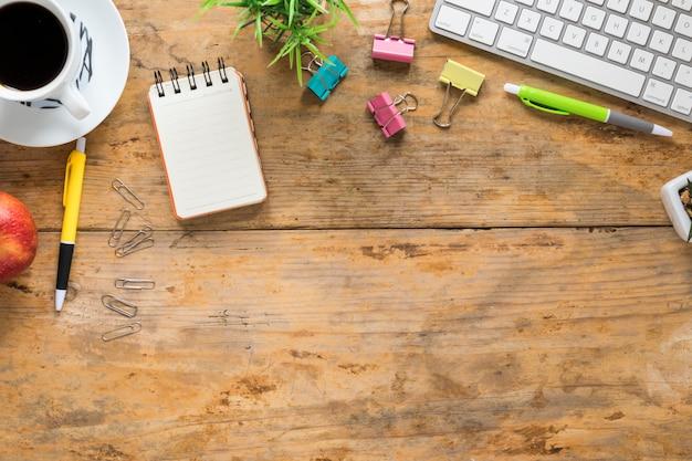 Xícara de café; maçã; artigos de papelaria de teclado e escritório na mesa de madeira Foto gratuita