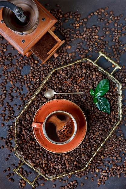 Xícara de café na bandeja com os feijões de café no fundo preto da tabela. vista de cima, close-up. Foto Premium