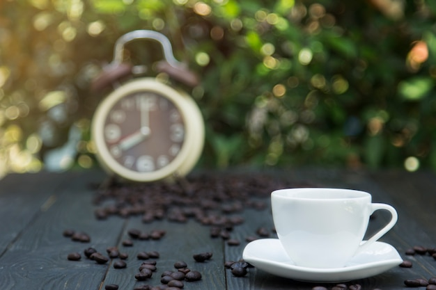 Xícara de café na mesa da manhã com grão de café e despertador fundo Foto Premium