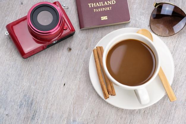 Xícara de café na mesa de madeira em um dia relaxante para tirar fotos, com câmera, passaporte e óculos de sol. Foto Premium
