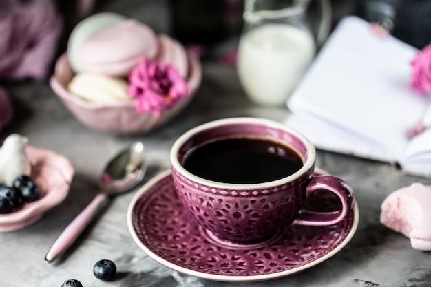 Xícara de café no café da manhã com marshmallows em forma de bolos de biscoito em uma tigela preta sobre uma mesa escura e com flores em um copo Foto Premium