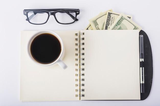 Xícara de café no notebook com óculos na mesa Foto gratuita