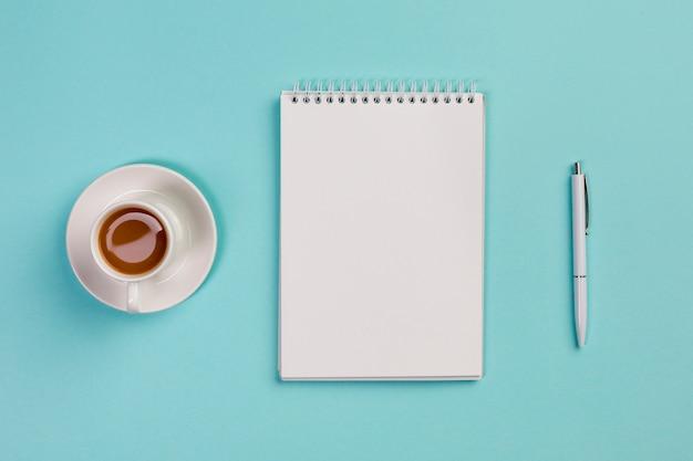 Xícara de café, o bloco de notas em branco em espiral e caneta na mesa de escritório azul Foto gratuita