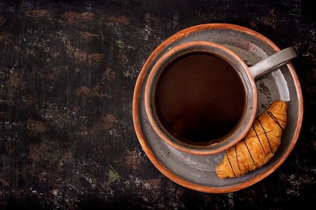 Xícara de café perfumado e um croissant. cafe da manha. lay plana. vista do topo Foto Premium