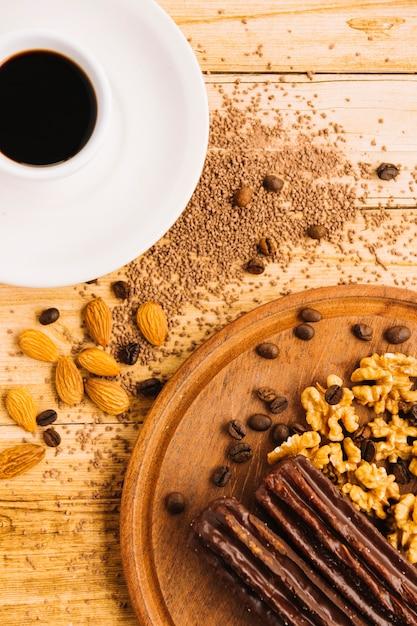 Xícara de café perto de nozes na tábua de cortar Foto gratuita