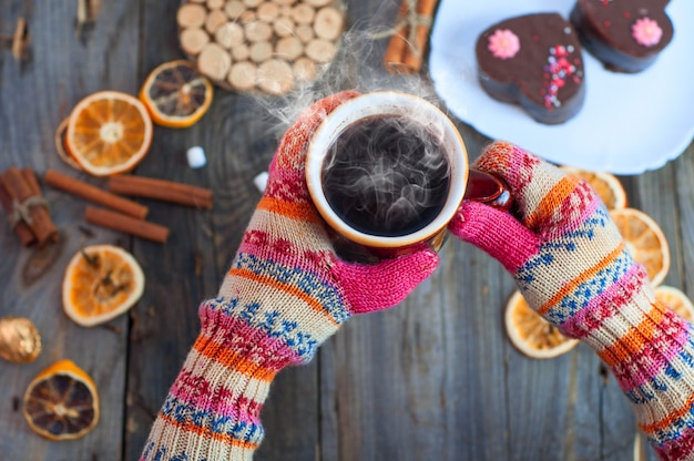 Xícara de café preto em suas mãos sobre a mesa Foto Premium