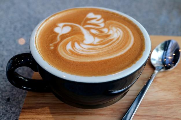 Xícara de café quente cappuccino com colher de chá, servido na bandeja de madeira Foto Premium