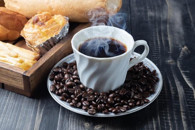 Xícara de café quente e grãos de café torrado Foto Premium