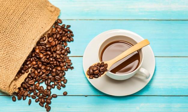 Xícara de café quente e grãos de café torrados do saco saco em uma mesa de madeira e colher. Foto Premium