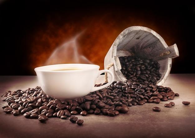 Xícara de café quente e grãos de café Foto Premium