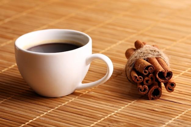 Xícara de café quente e paus de canela Foto gratuita