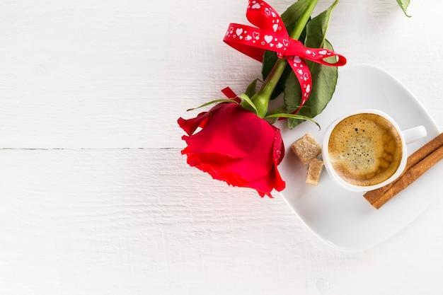 Xícara de café, rosa vermelha, açúcar e canela em um fundo branco de madeira Foto Premium