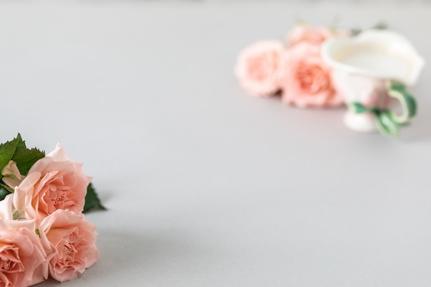 Xícara de café, rosas cor de rosa, rosas cor de rosa em um cinza Foto gratuita