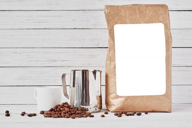 Xícara de café, saco de papel ofício e jarro inoxidável Foto Premium
